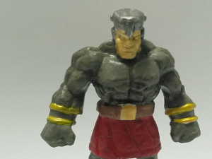 A stone golem mini from the front, painted grey, red and gold.
